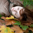 Young ginger lying on the autumn leaves — Foto de Stock