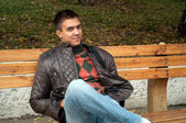 Young man sitting on a bench in park — Stock Photo
