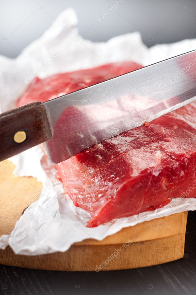 Knife cutting a large piece of uncooked beef — Stock Photo #1005760