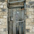 Grunge door in old stone house — Stock Photo
