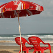 Royalty-Free Stock Photo: Red chairs and umbrella on the beach