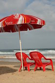 Red chairs and umbrella on the beach — Stock Photo