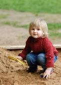 Criança brinca com areia — Fotografia Stock