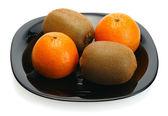 Kiwi and mandarin on a black plate — Stock Photo