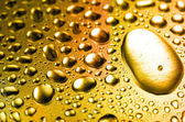 Golden close-up water drops background — Stock Photo