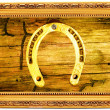 Royalty-Free Stock Photo: Gold horseshoe on an old wooden