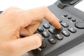 Fingers dialing number on telephone — Stock Photo