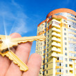 Gold keys with house on blue sky - Stock Photo