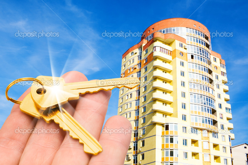 Real estate concept. gold keys in fingers with building — Stock Photo #1029175
