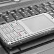 Stock Photo: Mobile phone lies on laptop keyboard