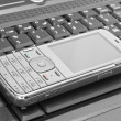 Mobile phone lies on the laptop keyboard — Stock Photo