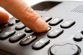 Dialing - telephone keypad with finger — Stock Photo