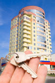 Building and key in hand — Stock Photo
