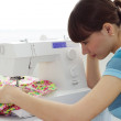 The girl works at sewing machine — Stock Photo