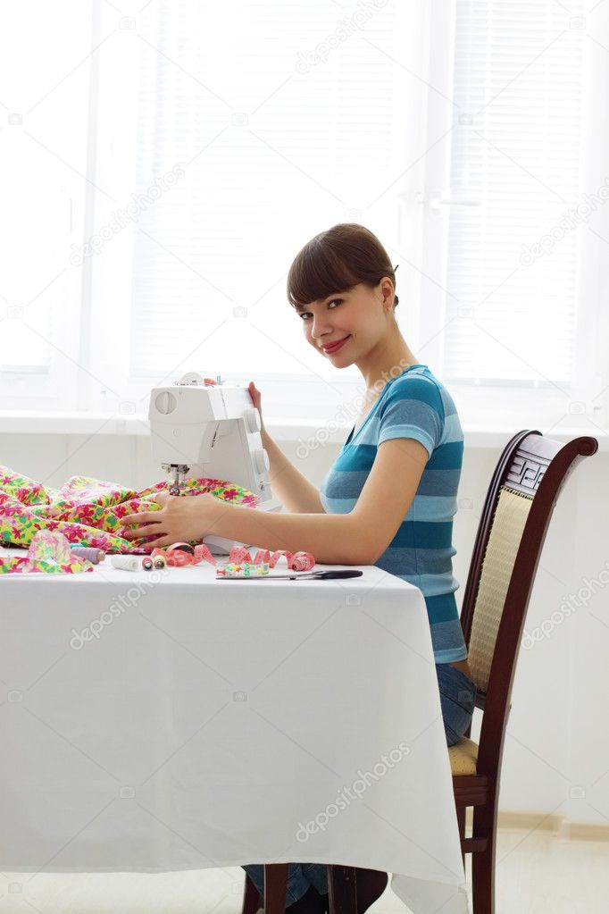 Girl sitting near a sewing machine — Stock Photo #2672269