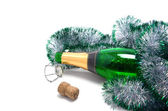 Bottle champagne and Christmas tinsel — Stock Photo