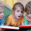 Kids reading the same book — Stockfoto