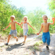 Happy kids running in the woods -  