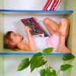 Stock Photo: Child reading a book in a bookcase