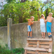 Stock Photo: Curious children spying over the fence