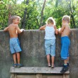 Curious children spying over the fence - Stock Photo