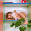 Child in a bookcase with a toy — Stock Photo