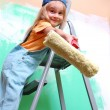 Child on ladder with a roller — Stock Photo