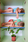 Tired kids in a closet — Stock Photo