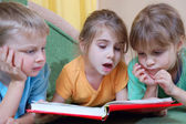 Kids reading the same book — Stok fotoğraf