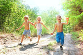 Happy kids running in the woods — Stockfoto