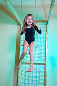Child at her home sports gym swinging — Stock Photo