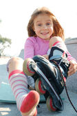 Child putting on her rollerblade skate — Stock Photo