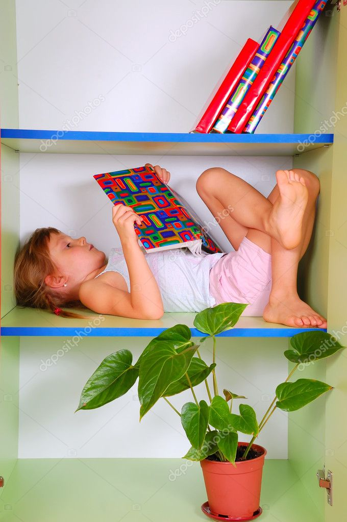 Little girl lying on a bookshelf and reading a book  — Stock Photo #1006189