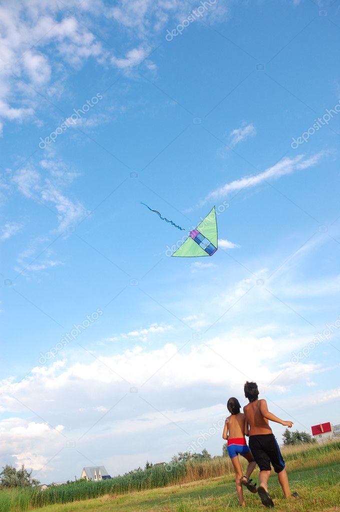 Two boys flying a kite in the summer meadow — Stock Photo #1007041
