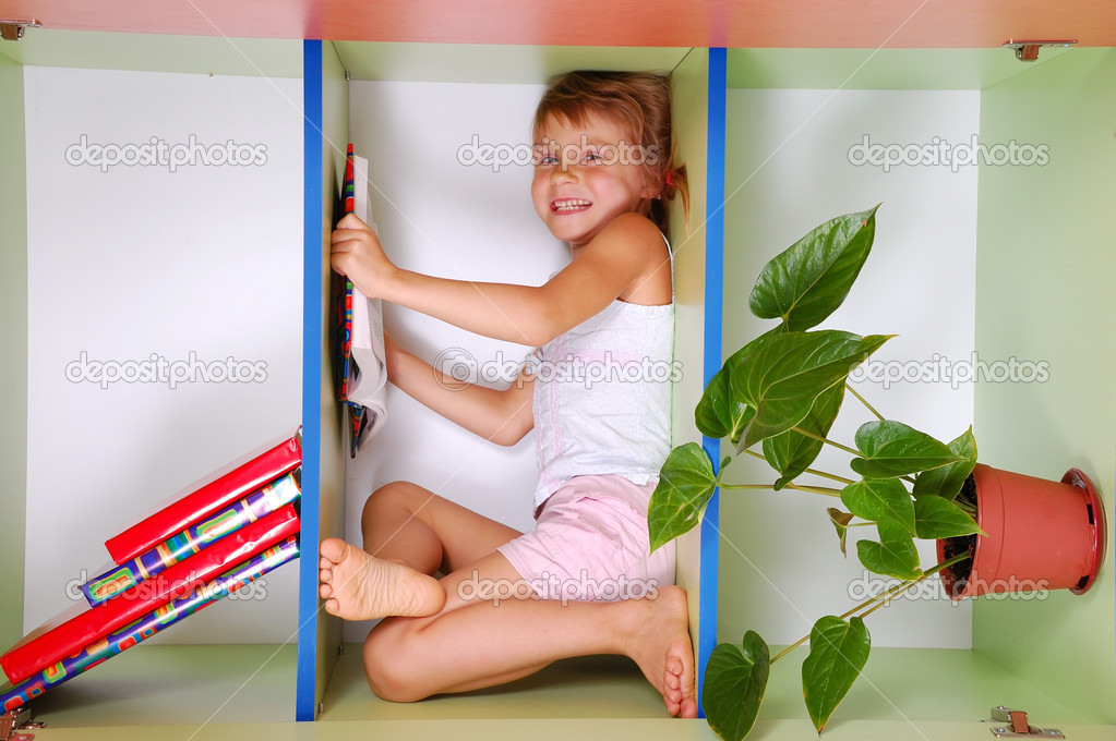 Smiling little girl lying on a bookshelf and reading — Stock Photo #1007316