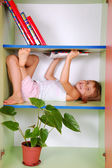 Child reading a book in a bookcase — Stock Photo