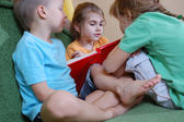 Three kids reading at home — Stock Photo
