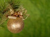 Palla di natale dorata su sfondo verde — Foto Stock