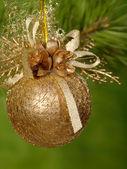 Boże narodzenie złoty piłkę na zielonym tle — Zdjęcie stockowe