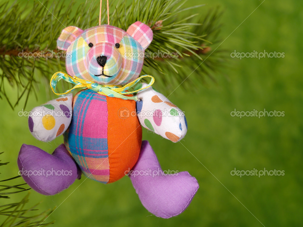 Xmas handmaded teddybear on the green background.  Stock Photo #1015915