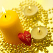 Holiday still life with candles on yello - Stock Photo