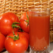 Fresh ripe tomatoes with glass of juice — Stock Photo