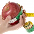 Red apple with tape measure in human han — Stock Photo