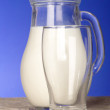 Milk jug close to glass on the table wit — Стоковая фотография