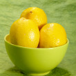 Fresh tasty lemon fruit on green backgro — Stock Photo
