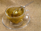Cup of green tea on hessian with honey s — Stock Photo