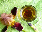 Cup pf tea with flower on green backgrou — Stock Photo