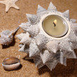 Still-life on the sea sand with candle a - Stock Photo