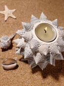 Still-life on the sea sand with candle a — Stock Photo