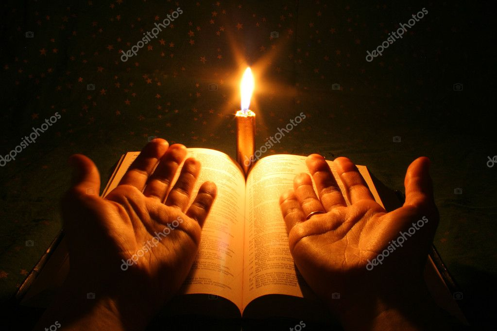 A bible open on a table next to a candle — Stock Photo #1016352